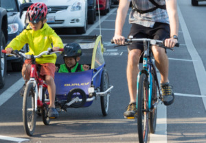 kid-riding-a-bike-with-a-trailer-behind-with-another-kid