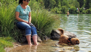 women with dog on the river