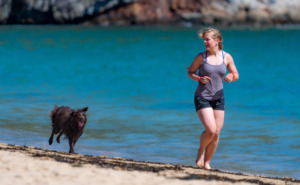 Woman and dog running on the seashor