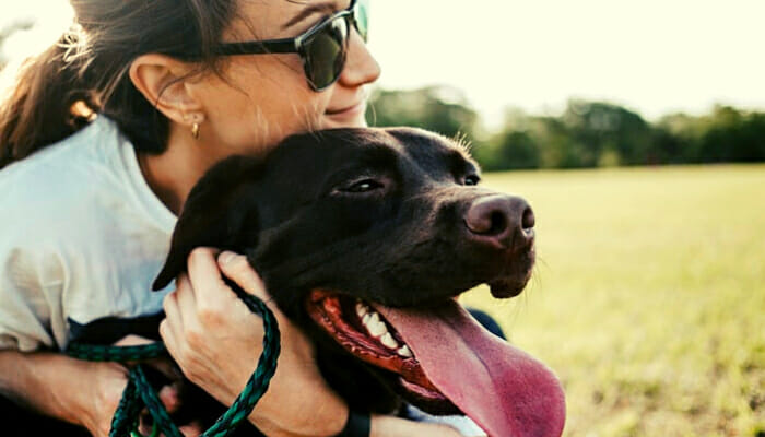 A woman dog owner hugging her dog tight